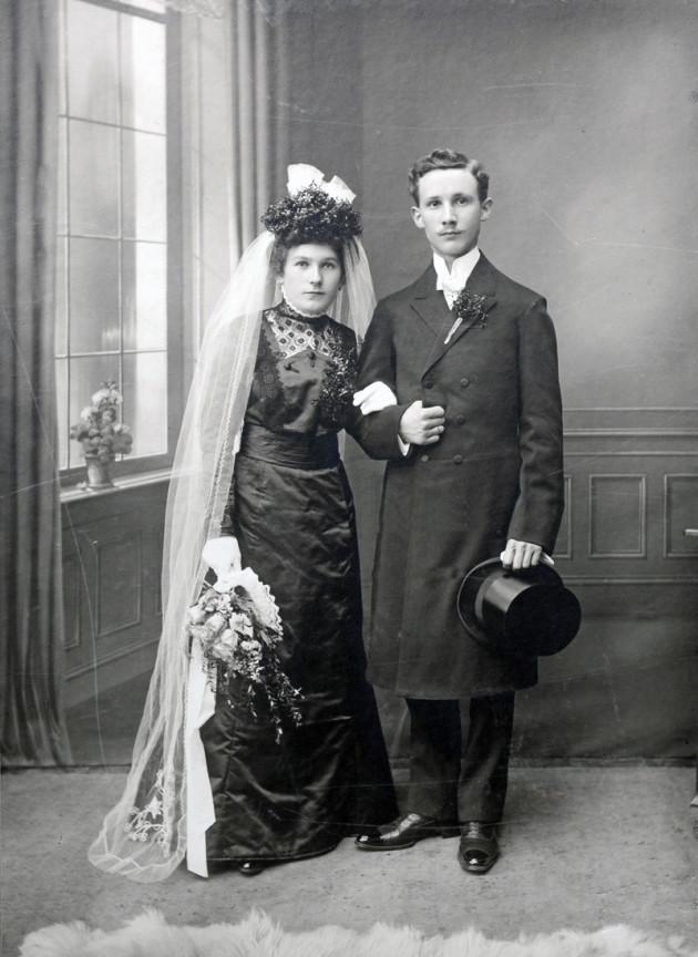 Zum Thema Ahnenforschung sieht man ein altes Foto mit einem Brautpaar, sie links er rechts, er hält einen Zylinder in der Hand. beide schauen zur Kamera.